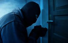 Masked Thief Using Lock Picker...