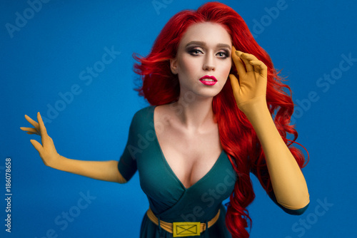 Photo  Beautiful woman in green superhero costume posing at camera on blue background
