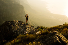 A Young Lady Trail Runner Watching The Sunset From A Mountain Top On The Cape Peninsula Of South Africa.
