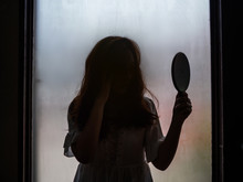 Ghost Girl Holding Mirror Standing In Front Of Window