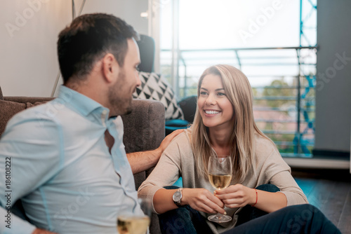 Cheerful couple sitting on floor and talking while looking at each other Canvas Print