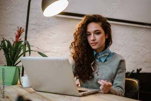 Concentrated young beautiful businesswoman working on laptop in bright modern office.