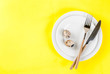 canvas print picture - Easter table setting. White plates, cutlery and quail eggs on yellow background. Top view copy space. Spring holidays concept