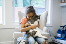 Girl Hugging Cat In Living Room