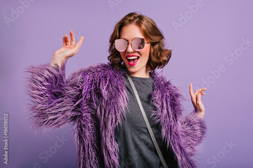 Stunning cute girl with curly brown hair posing with pleasure on purple background. Indoor photo of dancing young lady in trendy fur coat laughing to camera.
