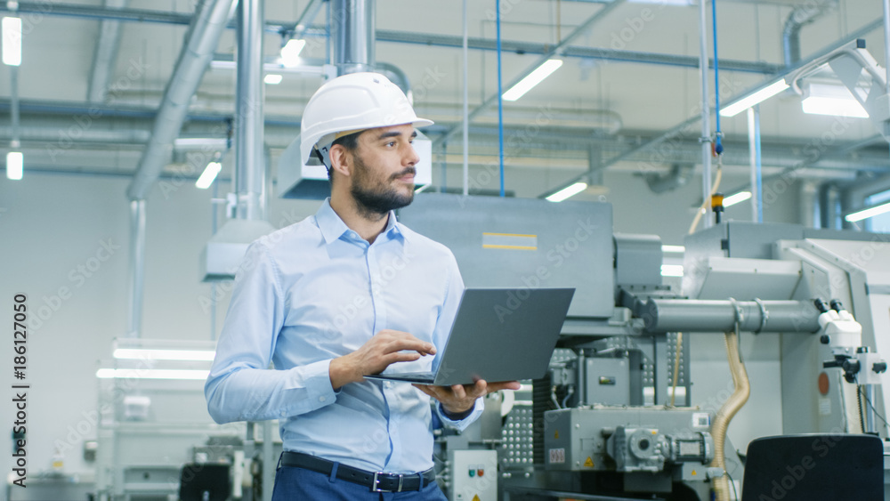 Fototapety, obrazy: Chief Engineer in the Hard Hat Walks Through Light Modern Factory While Holding Laptop. Successful, Handsome Man in Modern Industrial Environment.