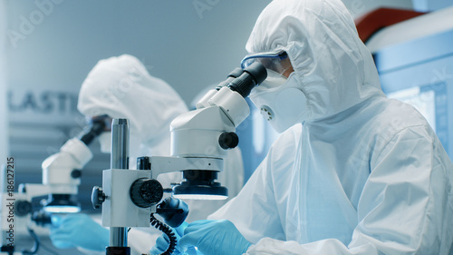 Fotomural  Two Scientists in Sterile Cleanroom Suits  Control Manufacturing Machinery Work and Use Microscopes for Component Adjustment and Research