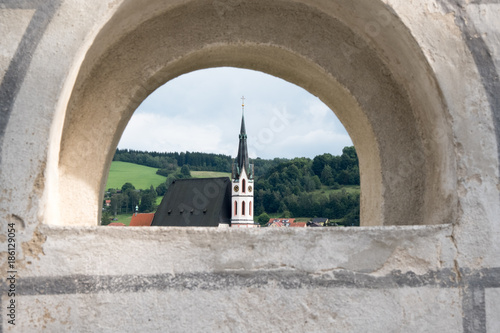 Poster Oost Europa View of the charming medieval town, Cesky Krumlov, from the castle. Looking at Kostel sv Vita (Church of St Vitus) through a narrow archway, framing the church on a summer's day. Quaint Czech town.
