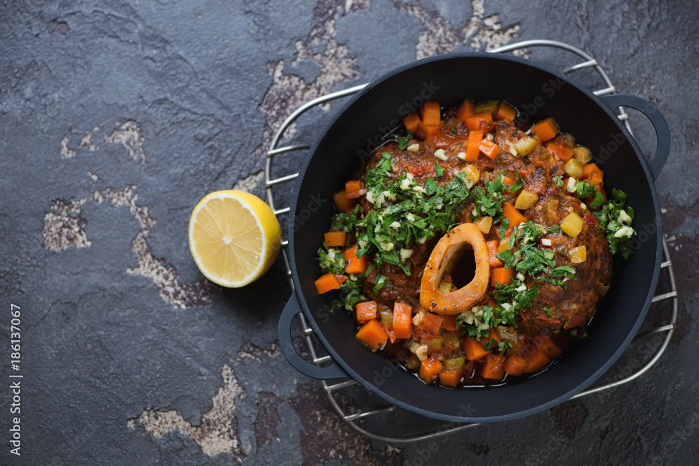Fototapety, obrazy: Cast-iron pan with ossobuco made of cross cut veal shank, view from above on a brown stone background, copyspace