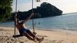 Happy man having fun on swing on beach, super slow motion 240fps