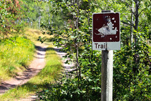 A Shot Up Trail Sign With A Ro...