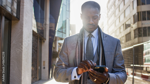 Fotografia  Handsome professional male walking in the city using his phone