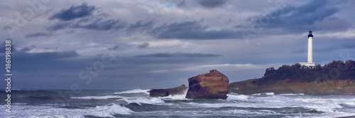 Photo Lighthouse of Biarritz under a dark sky with clouds and a rough sea