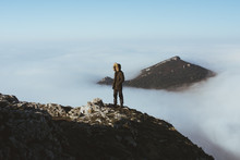 Man On Rocky Cliff In Clouds