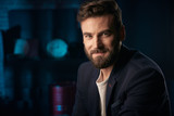 Portrait of happy handsome man with dark hair, beard and mustache wearing dark jacket. Studio shot with blue lighted brick background with blurred clock and red barrel