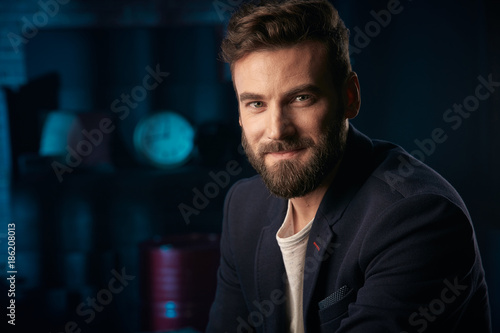 Portrait of happy handsome man with dark hair, beard and mustache wearing dark jacket Poster