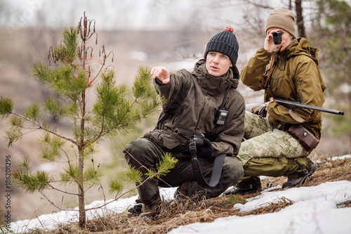 Foto op Canvas Jacht male and woman hunters ready to hunt, holding gun and walking in forest.