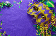 canvas print picture - Mardi Gras border or frame of carnival masks, beads, ribbons and confetti in purple, green, gold and black on background of rough textured sparkly paper
