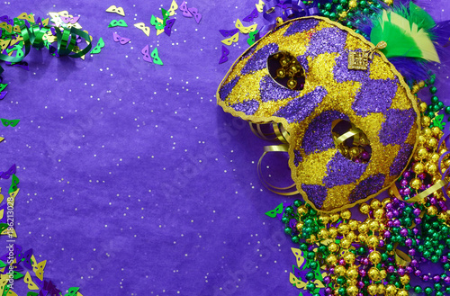 Tuinposter Carnaval Mardi Gras border or frame of carnival masks, beads, ribbons and confetti in purple, green, gold and black on background of rough textured sparkly paper