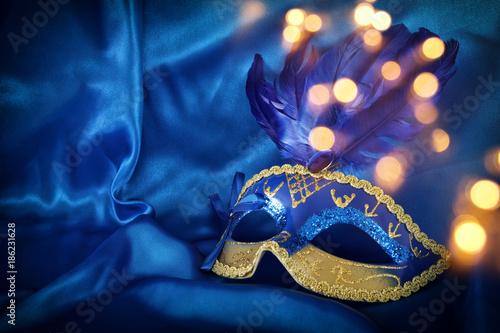 Image of elegant venetian mask over blue silk background.