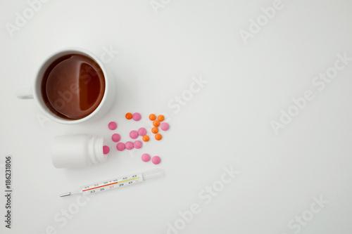 Fototapeta on a white background thermometer, tablets and tea. Space for text obraz na płótnie