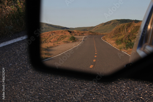 Looking into a rearview mirror at a landscape image of a deserted, divided highway heading towards the Northern California foothills near Petrolia Canvas Print