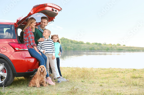 Fotografia, Obraz  Young family with cute children and dog near car