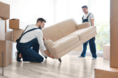 Fotografiet  Delivery men moving sofa in room at new home
