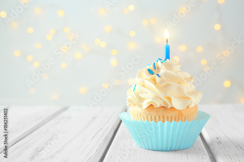 Photo  Tasty cupcake with candle on wooden table