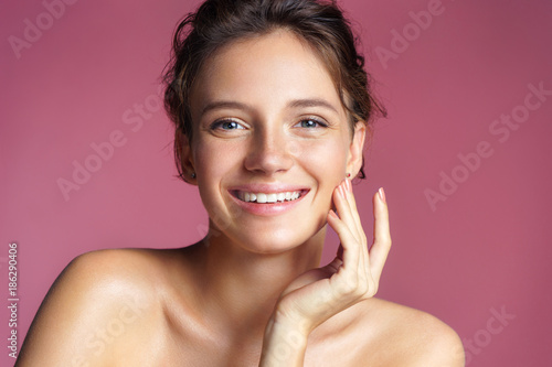 Fotografiet  Beautiful young girl touching her perfect skin on pink background