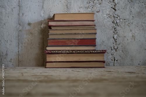 pila di libri antichi su tavolo legno grezzo e muro grezzo Fototapet