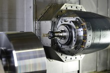 The 5-axis CNC Machine While Cutting The Sample Part Of Turbine.The Spindle Of 5 Axis CNC Machining Center White Cutting Turbine Sample Part.