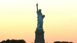 golden sunset and a silhouetted statue of liberty in new york