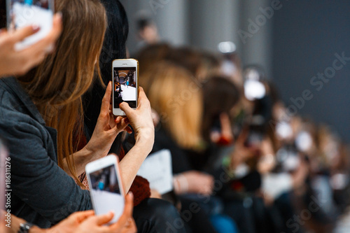 Fotomural Woman making photo on smatrphone while watching fashion show