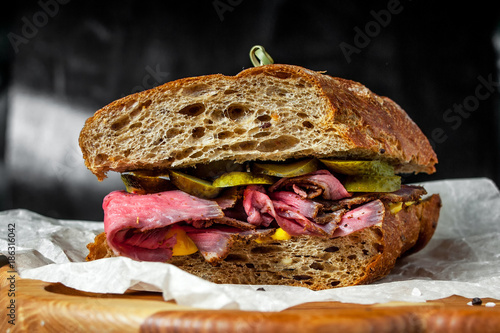 Staande foto Snack Pastrami sandwich on rye bread with pickles and mustard sauce, served on wooden plate