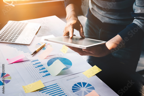 Fotomural  business man holding  digital tablet and use laptop to working document accountant analyze income & budget & tax is are planning a marketing plan to improve the quality of their sales in the future