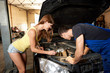 A sexy girl helps an auto mechanic repair a car in a garage. The girl is frankly dressed holding a flashlight under the open hood