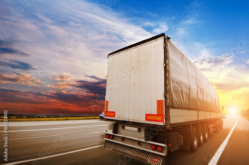 Fotografie, Obraz  Semi truck with a white trailer driving fast on the countryside road against a n