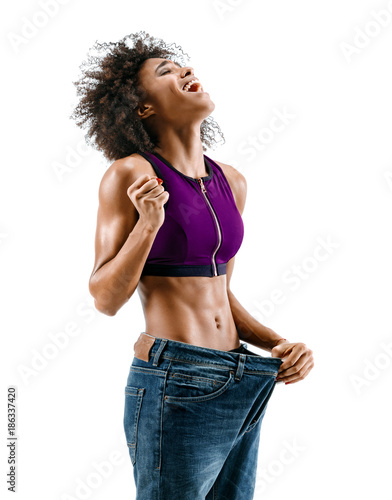 Fotografía  Sporty girl pulling her big jeans and showing weight loss