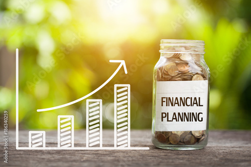 Fotomural Financial planning word with coin in glass jar and graph up.