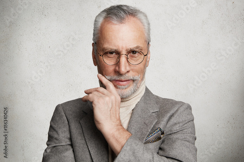 Pleased handsome wrinkled mature man wears spectacles and formal suit, looks directly into camera with confident expression, being glad to be promoted, isolated over white concrete background