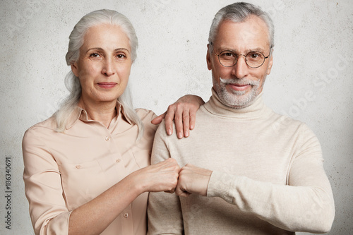 Láminas  Mature beautiful woman and handsome bearded man express agreement, touch fists, isolated over white concrete background