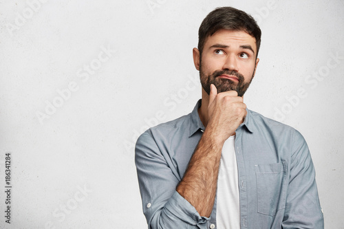 Fotografía  Thoughtful man with stubble looks pensively upwards, has pleasant dreams as plan