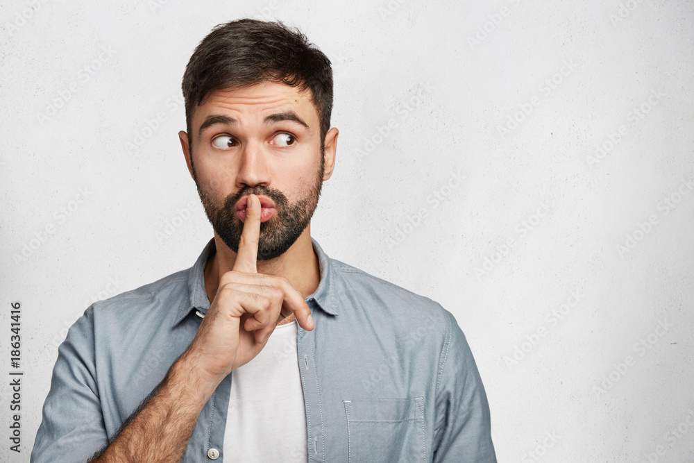 Fototapeta Serious good looking male with trendy hairdo, keeps fore finger on lips, tries to keep conspiracy, looks aside, says: Shh, make silence please. Isolated shot of attractive man shows silence sign