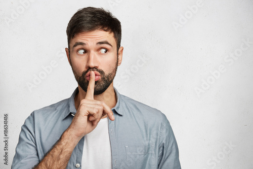Obraz na plátně Serious good looking male with trendy hairdo, keeps fore finger on lips, tries to keep conspiracy, looks aside, says: Shh, make silence please