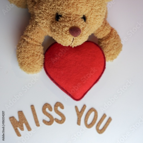 Foto Top view brown teddy bear holding red heart with the word miss you in front on w