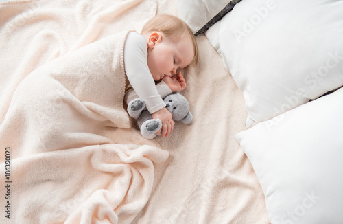 Fotografía  Top view of peaceful baby lying at sheets and sucking her finger