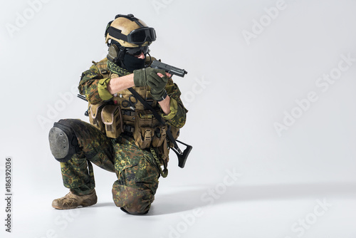 Tuinposter Helicopter Portrait of serious defender kneeling while shooting with gun. Protection and attack concept. Copy space