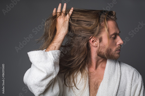 Fényképezés  Profile of young bearded guy holding his long tangled locks among fingers
