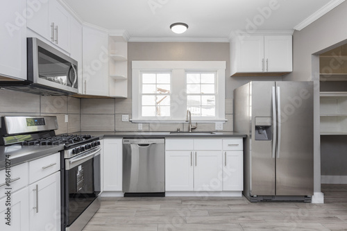Kitchens in white new, with granite counter-tops, stove and stainless steel refrigerator Wallpaper Mural
